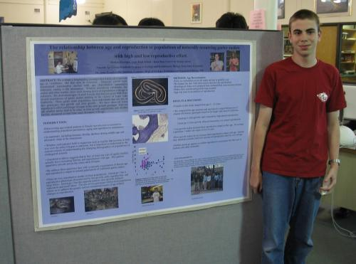 Photograph of a student next to his research poster